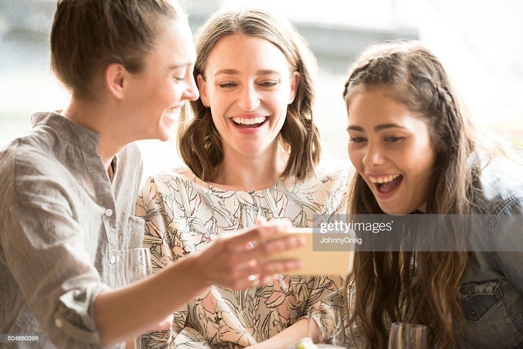 Young woman showing two female friends mobile phone : Stock Photo
