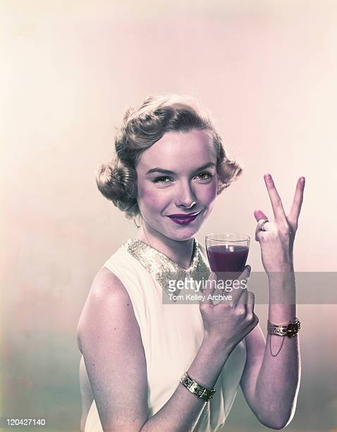 young woman showing v sign with wine glass, smiling, portrait - archival stock pictures, royalty-free photos & images