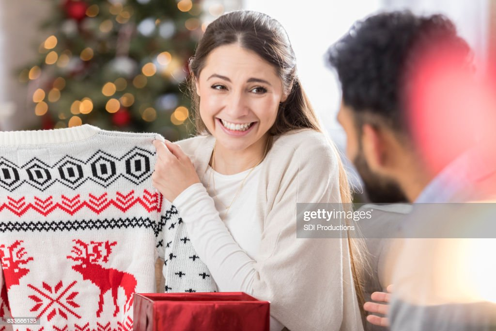 Young woman shows disappointment in Christmas gift : Stock Photo