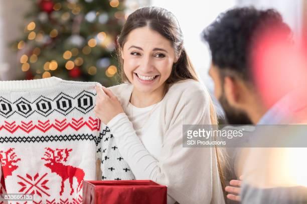 Junge Frau zeigt Enttäuschung in Weihnachtsgeschenk