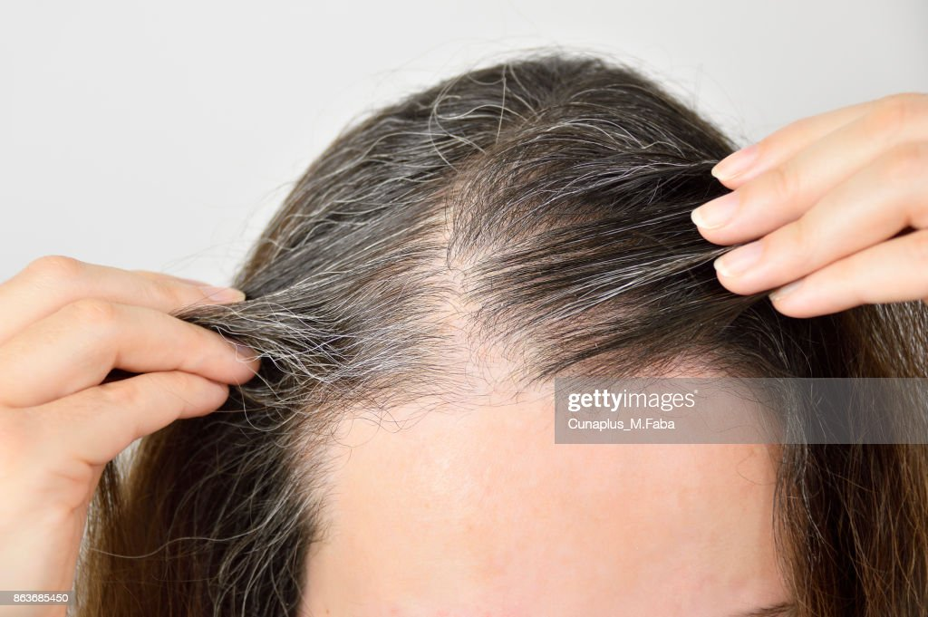Young woman shows her gray hair : Stock Photo