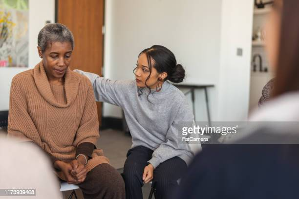 young woman shows support in therapy session - grief stock pictures, royalty-free photos & images