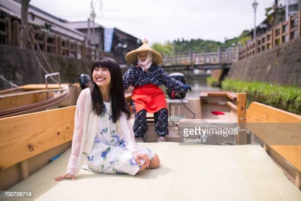 ボートに乗って観光する若い女性