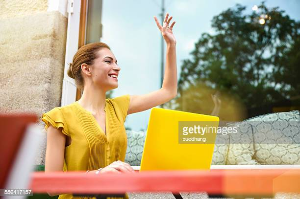 Young woman signalling to waiter, using laptop outside cafe