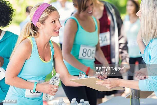 Junge Frau Unterzeichnung für marathon oder 5 k charity-Rennen