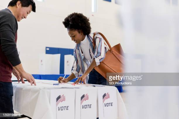 young woman signs up to vote as volunteer watches - voting stock pictures, royalty-free photos & images