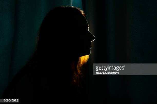 young woman silhouette in dark. - silhouette stock pictures, royalty-free photos & images
