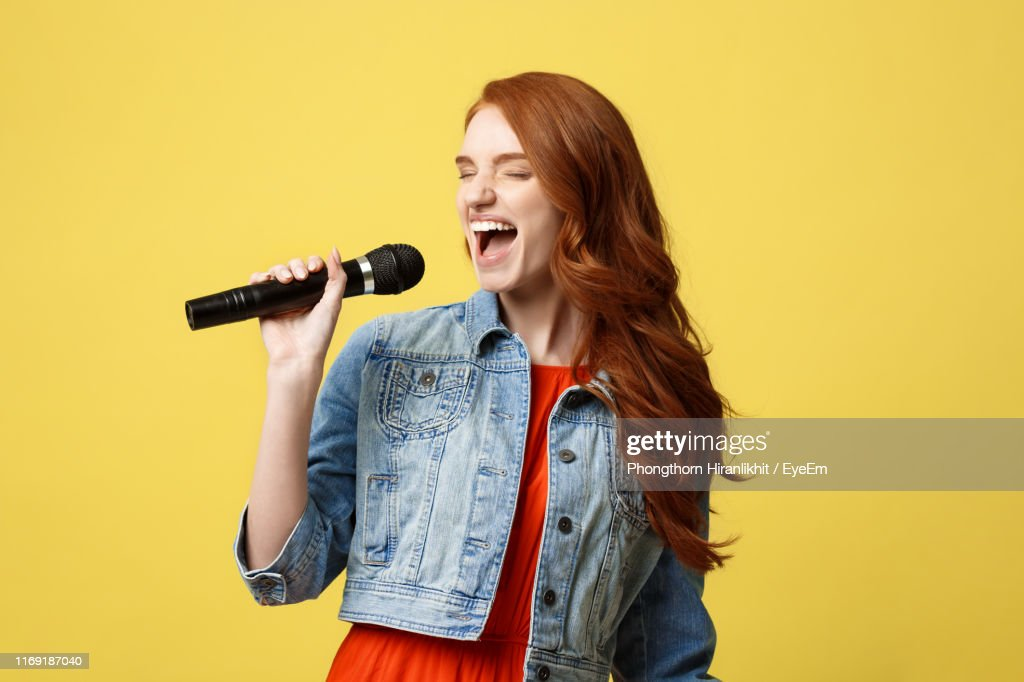Young Woman Singer Singing While Standing Against Yellow Background : Stock Photo