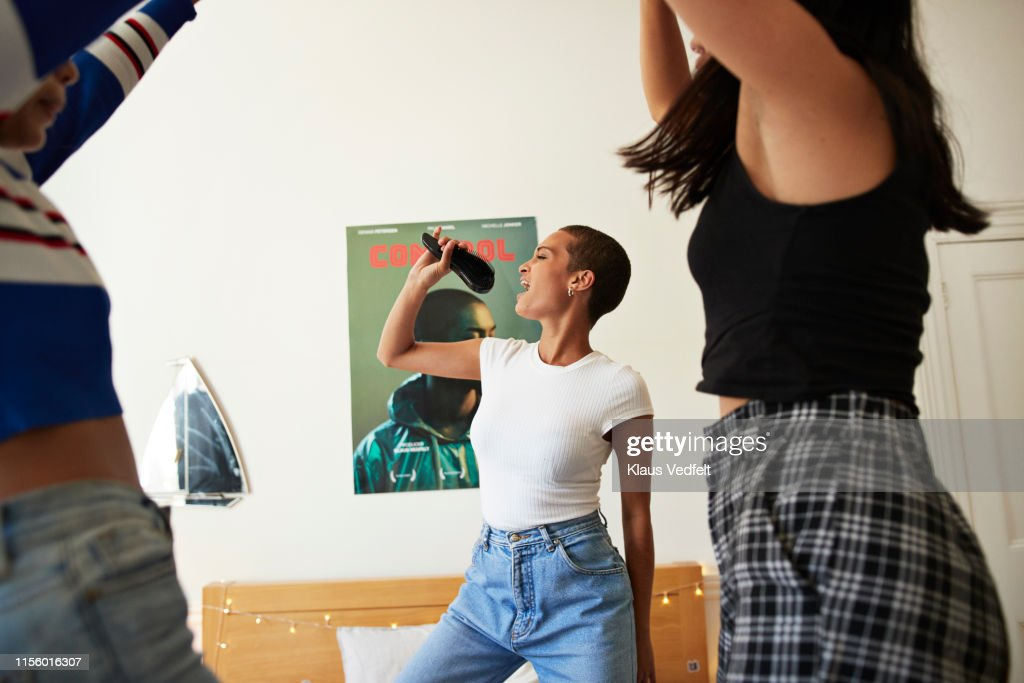 Young woman singing and dancing with friends : Foto de stock