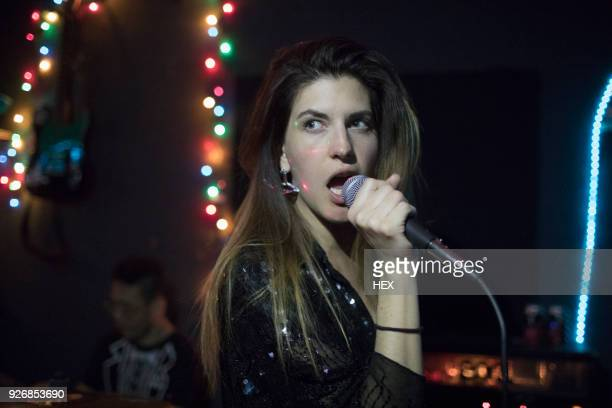 young woman singing at band rehearsal - rehearsal stock pictures, royalty-free photos & images