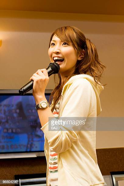 Young woman singing at karaoke booth