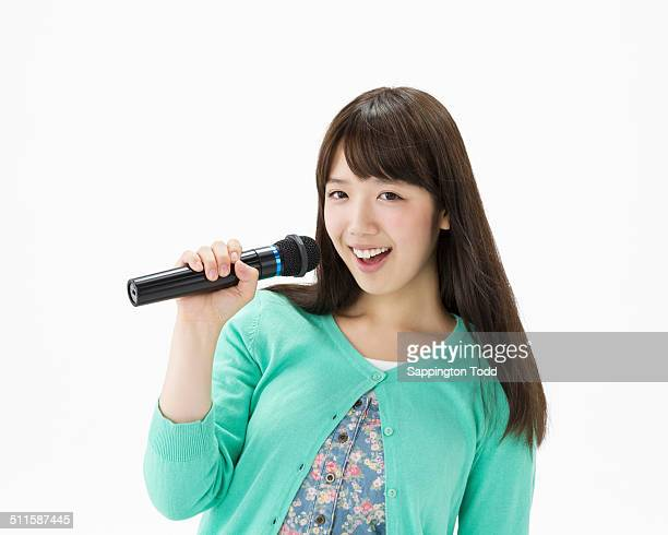 Young Woman Singing Holding Microphone
