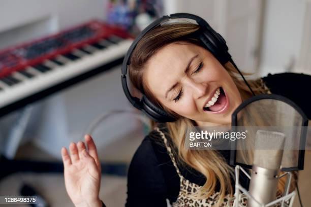 young woman singing in home recording studio - ルポルタージュ ストックフォトと画像