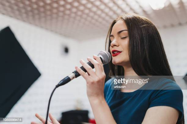 young woman singing in recording studio - rehearsal stock pictures, royalty-free photos & images