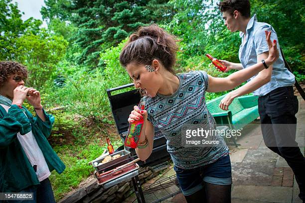 Young woman singing into bottle at a backyard barbecue