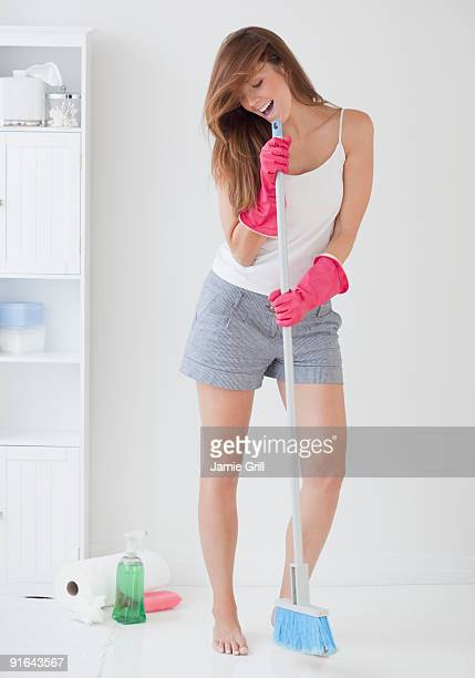 Young woman singing into broom while cleaning