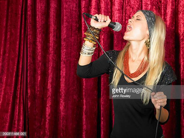 Young woman singing into microphone, eyes closed