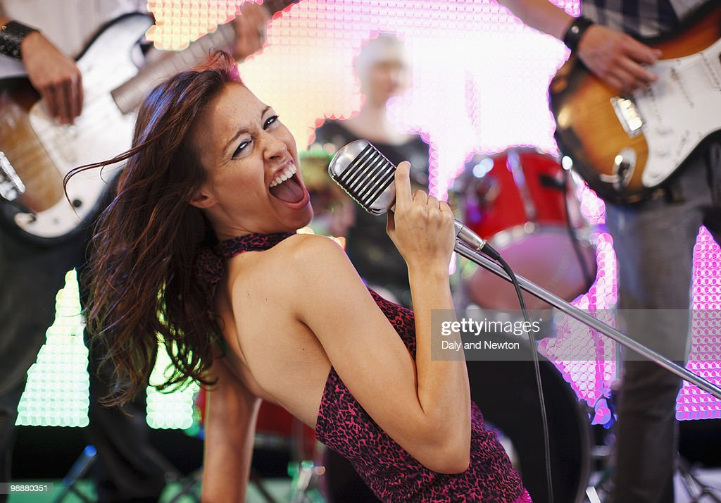 Young woman singing into microphone with rock band : Stock Photo