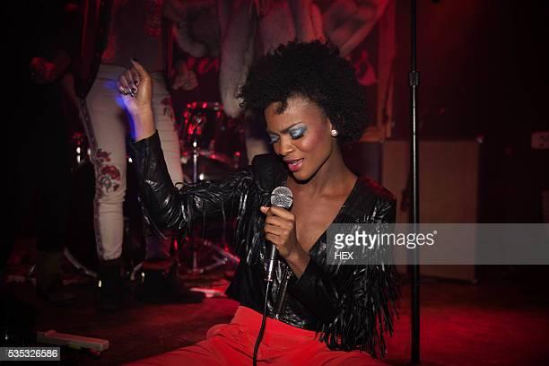 young woman singing karaoke - karaoke stockfoto's en -beelden