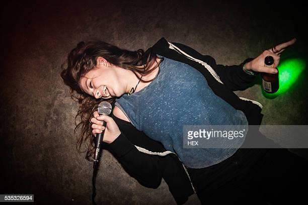 young woman singing karaoke - femme saoule photos et images de collection