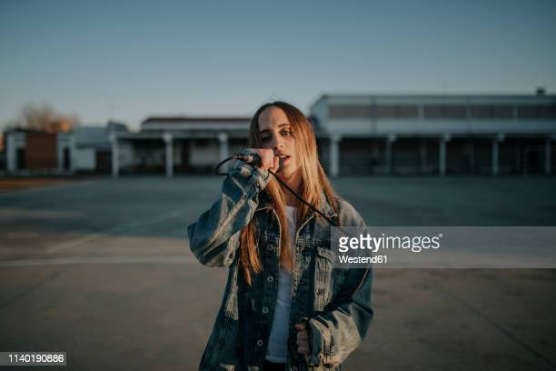 young woman singing with a microphone on school yard - singer stock pictures, royalty-free photos & images