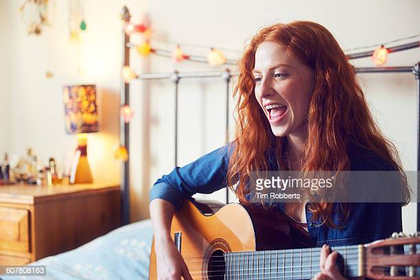 young woman singing with guitar - singing stock pictures, royalty-free photos & images