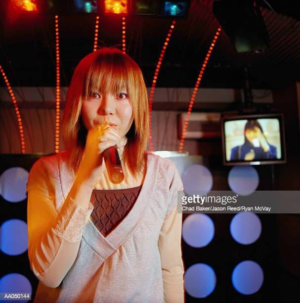 Young woman singing with microphone, portrait