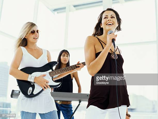 young woman singing with two young women playing musical instruments - girl band stock pictures, royalty-free photos & images