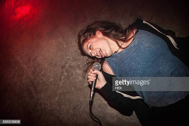 young woman sings in bar - karaoke stock pictures, royalty-free photos & images
