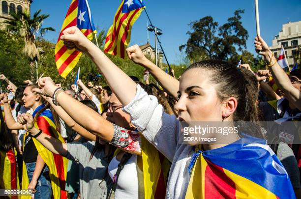 A young woman sings the catalan anthem in University square while raising her arm in the air Thousands of students have rallied in support of the...