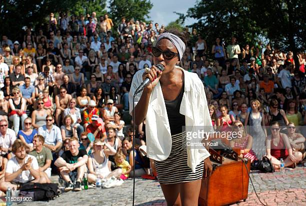 A young woman sings to an audience of hundreds during the weekly summer openair karaoke sessions in Mauerpark park on June 5 2011 in Berlin Germany...