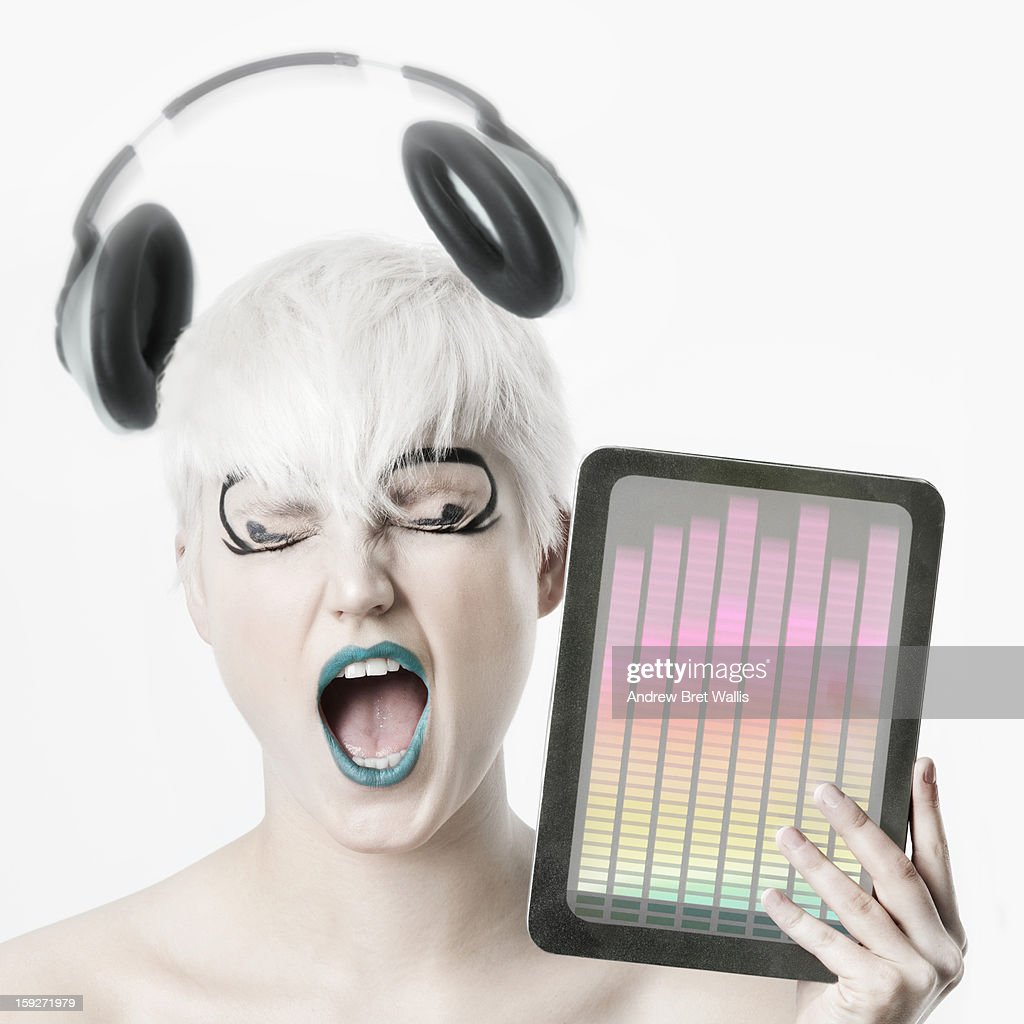 young woman sings to music on computer tablet : Stock Photo