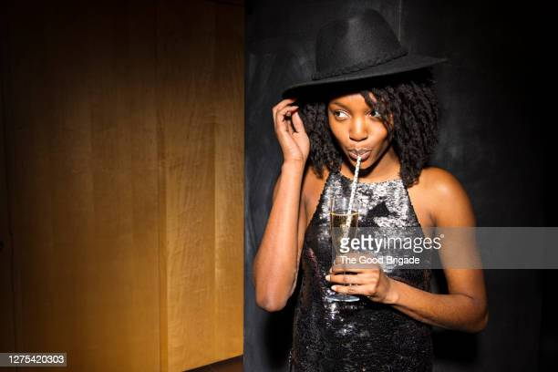 young woman sipping champagne from a straw - sequin stock pictures, royalty-free photos & images