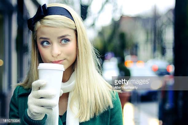 若い女性のコーヒーを飲みながらの手袋を装着するとスカーフ