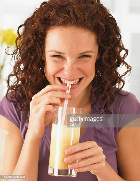 Young woman sipping fruit juice, smiling