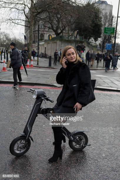 A young woman site on her CleveYoung cBike while using her phone in the street on 4th February 2017 in London United Kingdom The 40lb CleveYoung...