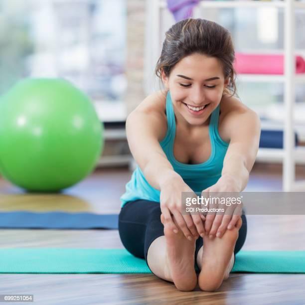 jeune femme est assise et touche les orteils pendant les exercices au sol - gymnastique au sol photos et images de collection