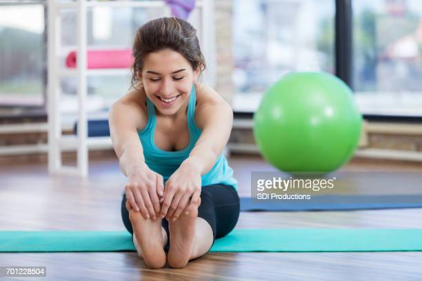 Young woman sits and touches toes during floor exercises