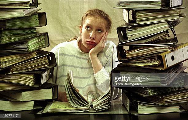 Young woman sits at a desk between stacks of files She is supporting her head with her elbow looking desperate