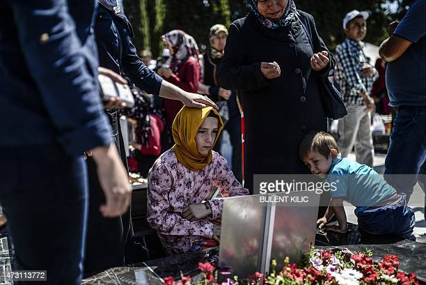 Young woman sits at by a grave as relatives and friends gather at the cemetery in the Turkish town of Soma in the Manisa district, western Turkey, on...