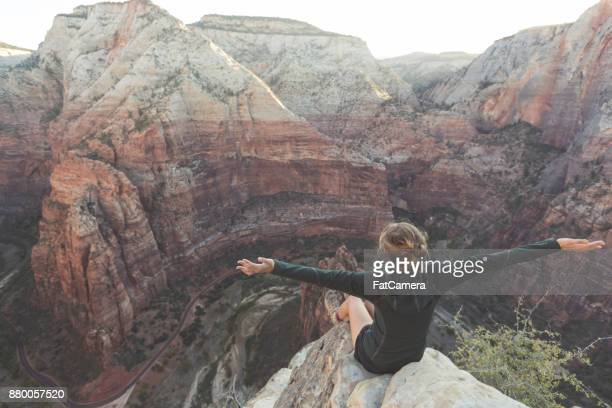 Young woman sits at the edge of a cliff overlooking highway