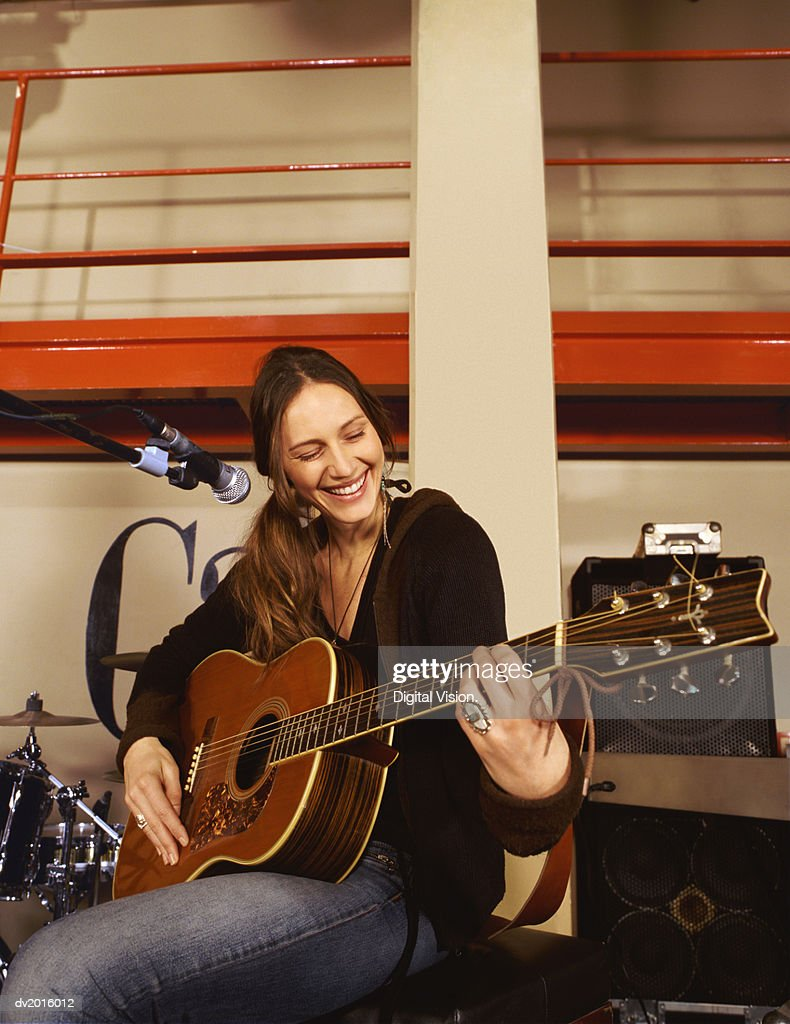 Young Woman Sits by a Microphone Stand on a Stage, Playing a Guitar and Smiling : Stock Photo