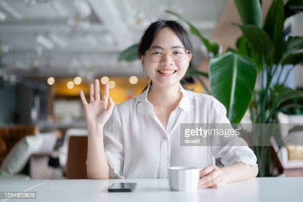 young woman sits by table - 手を振る ストックフォトと画像