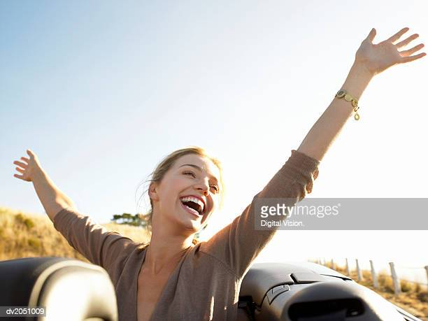 young woman sits in the back of a convertible, her arms in the air, laughing with joy - free stock photos and pictures