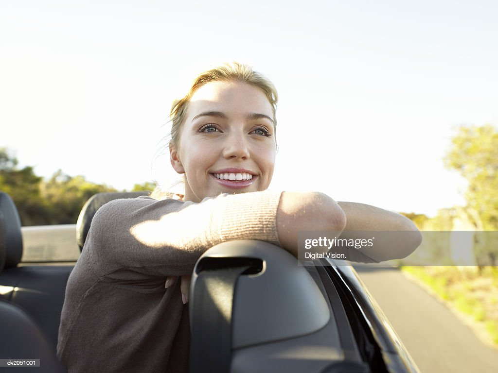 Young Woman Sits in the Back Seat of a Convertible Smiling at the View : Stock Photo