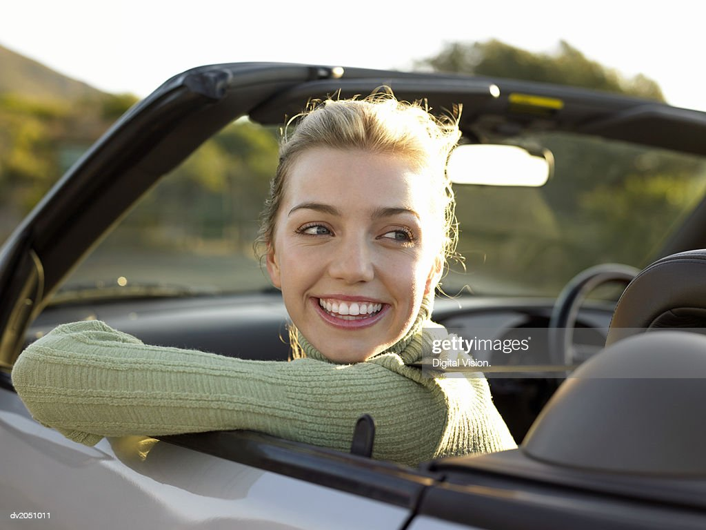 Young Woman Sits in the Front Passenger Seat of a Convertible, Looking Back and Smiling : Stock Photo