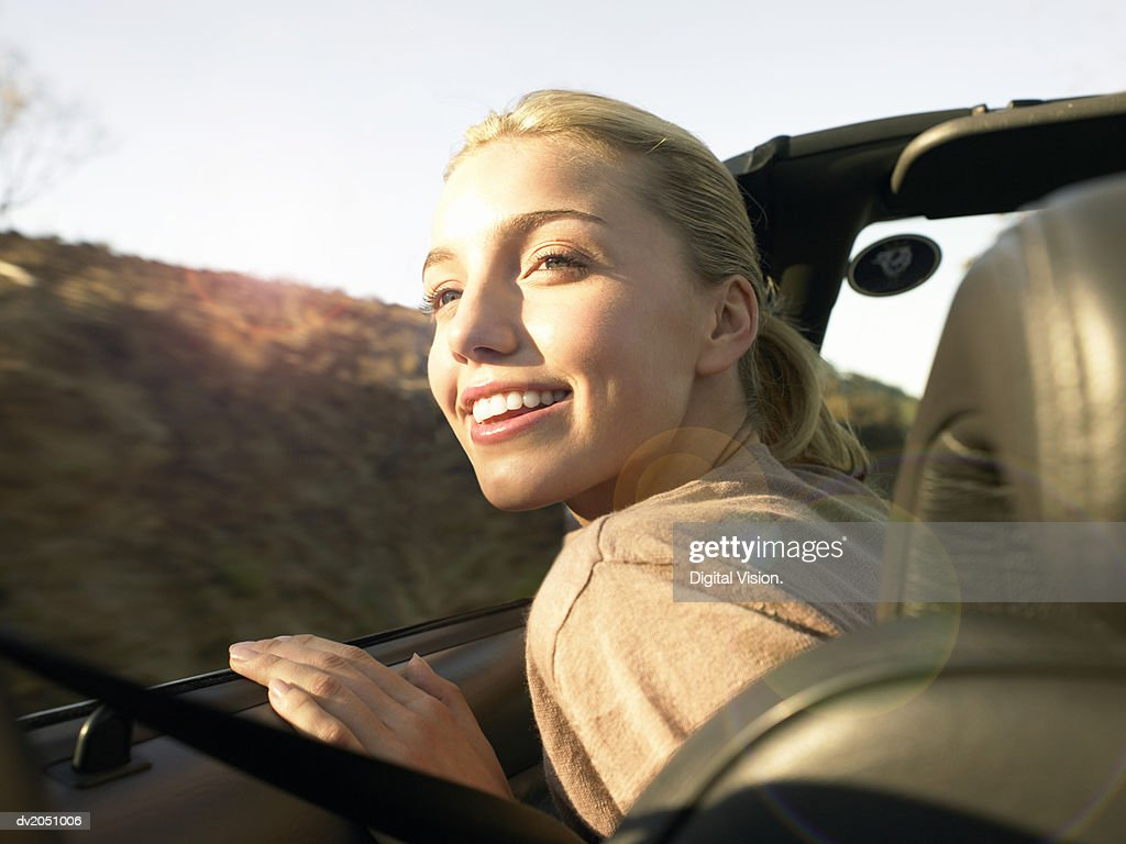 Young Woman Sits in the Front Seat of a Convertible Looking at the View : Stock Photo