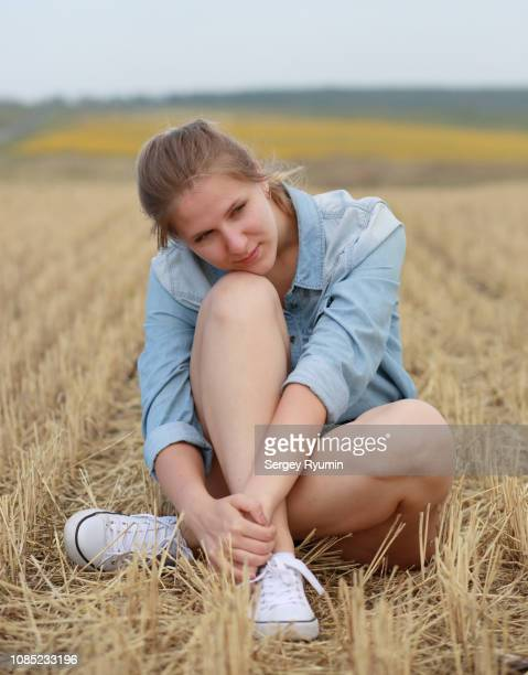 Young woman sits in the middle of a mown field.