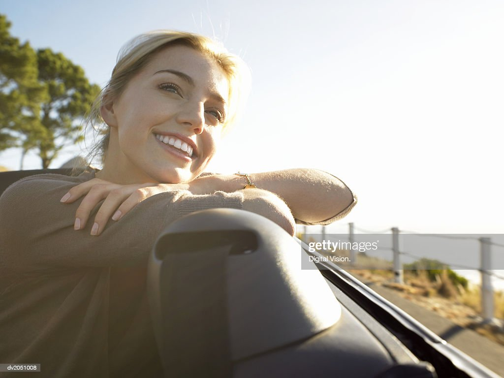 Young Woman Sits in the Rear Seat of a Convertible, Smiling at the View : Stock Photo