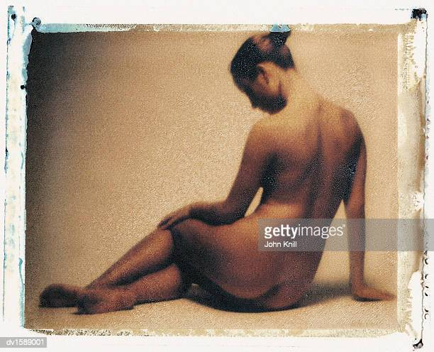 Young Woman Sits Leaning on One Arm, Naked and Looking Down